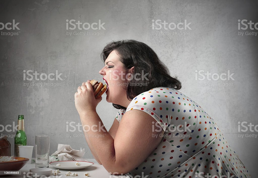 An obese woman eating a hamburger and being gluttonous royalty-free stock photo