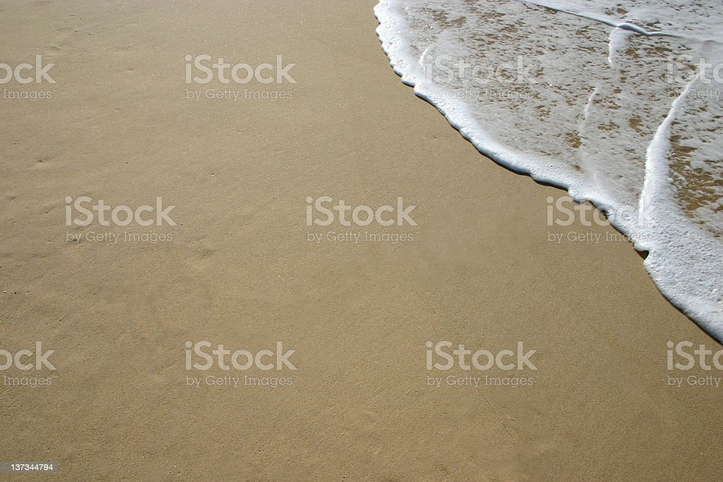 An ocean wave hitting the beach shore royalty-free stock photo