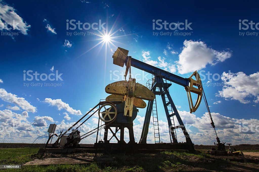 An oil and gas well against a sunny sky stock photo