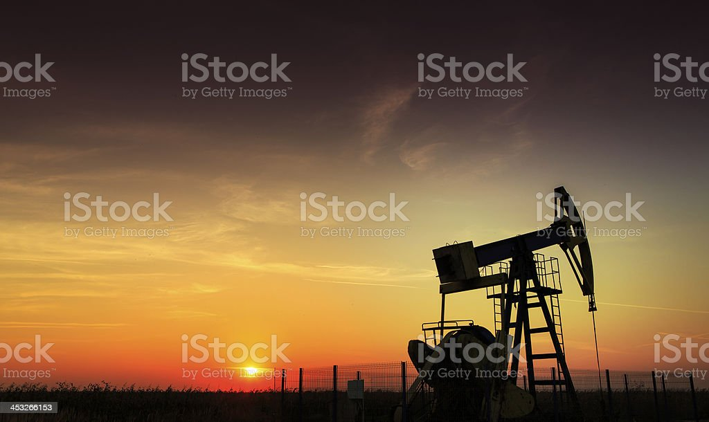 An oil and gas well operating during sunset stock photo