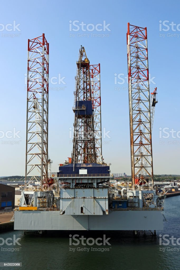 An oil rig in a harbor by the sea. A drilling rig in the sea stock photo