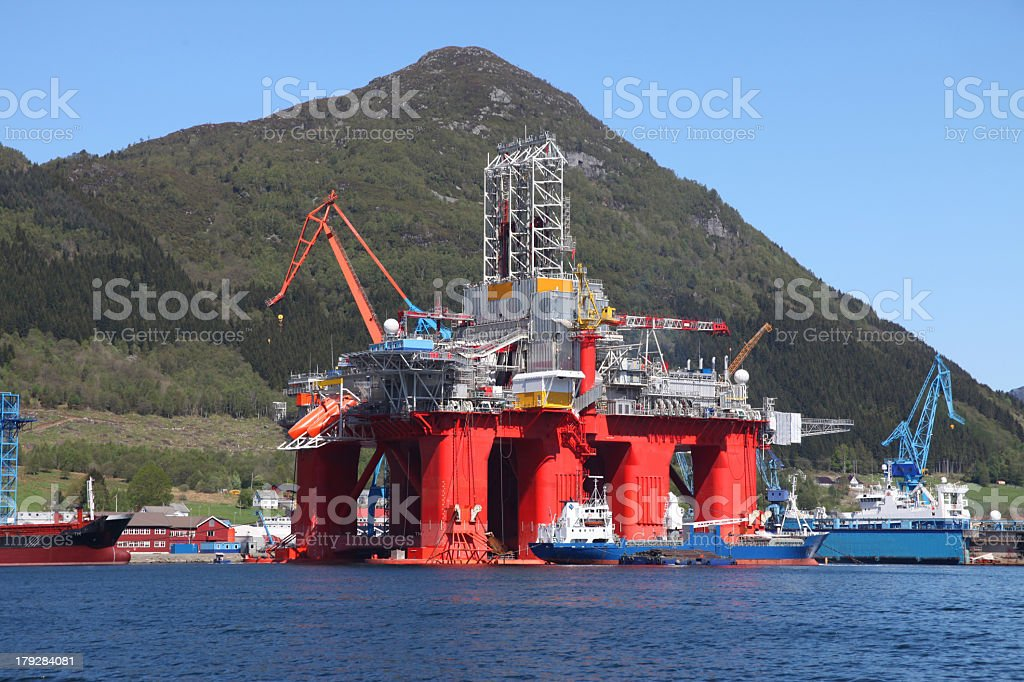 An oil rig in the water in front of a mountain stock photo