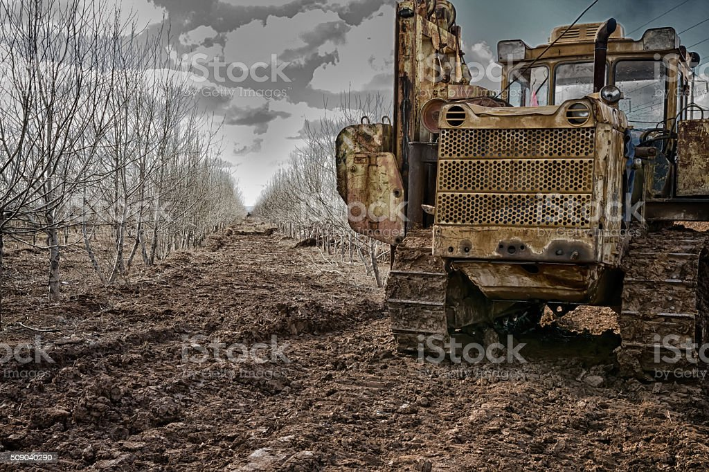 An old abandoned tractor standing near the dark thickets without stock photo