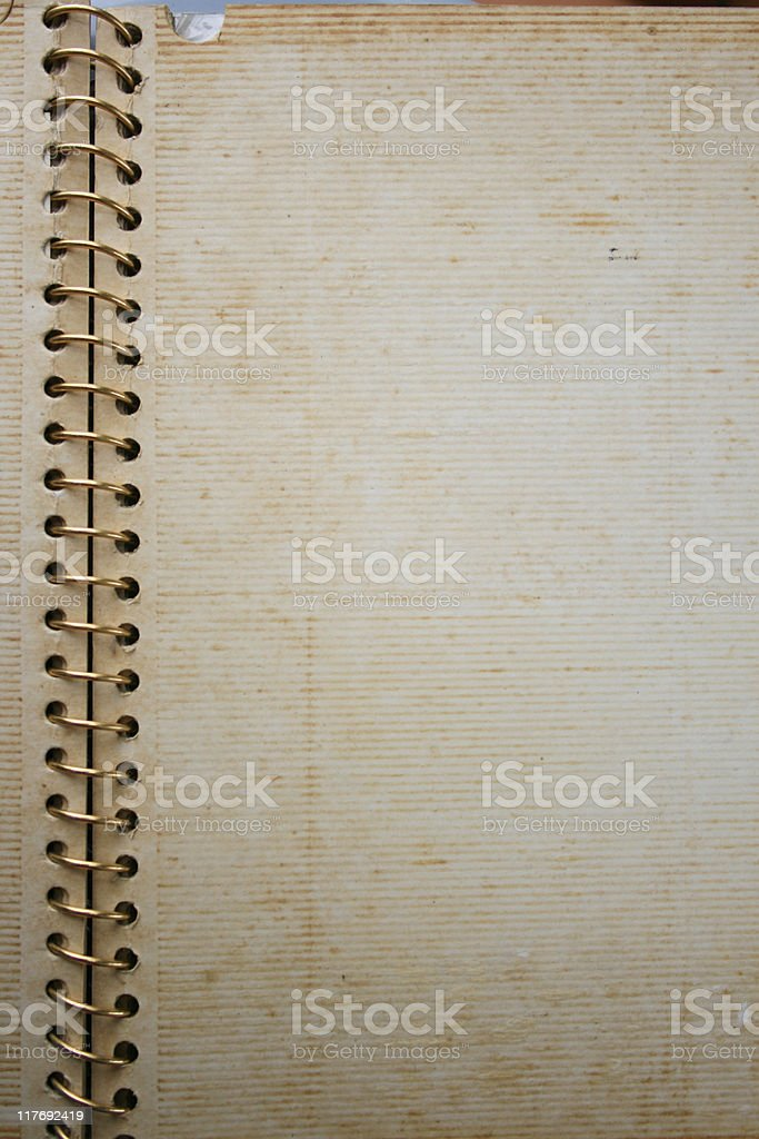 An old album with a gold spiral spine, open to a blank page stock photo