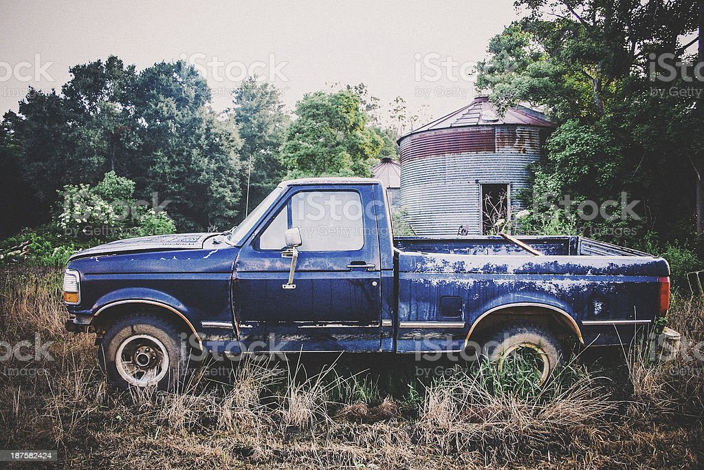 An old blue rusty truck in a field stock photo