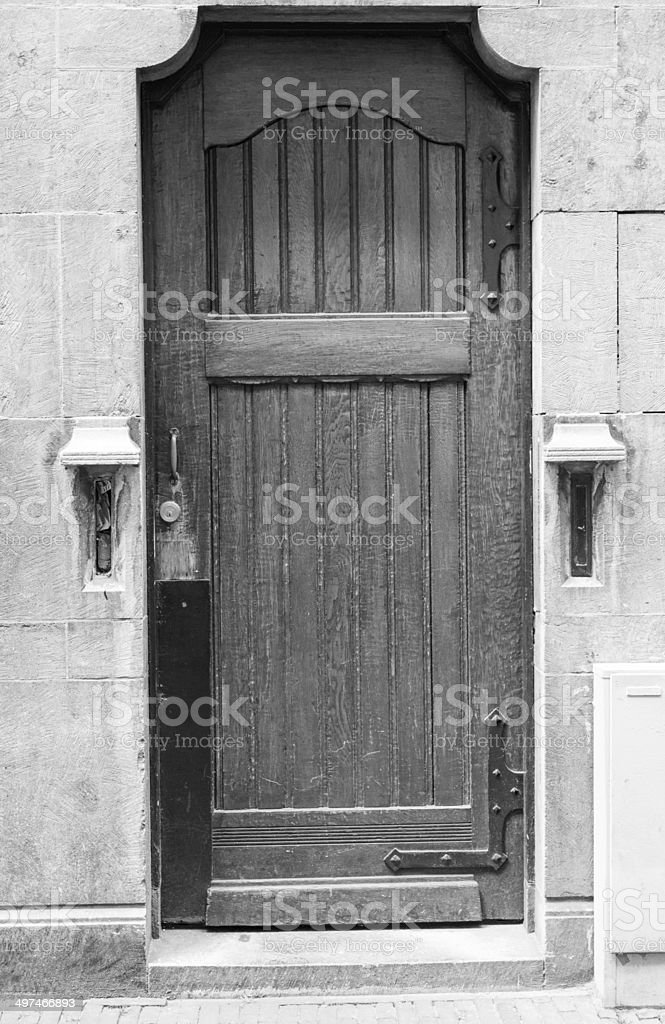 An old brick wall with black wooden door stock photo