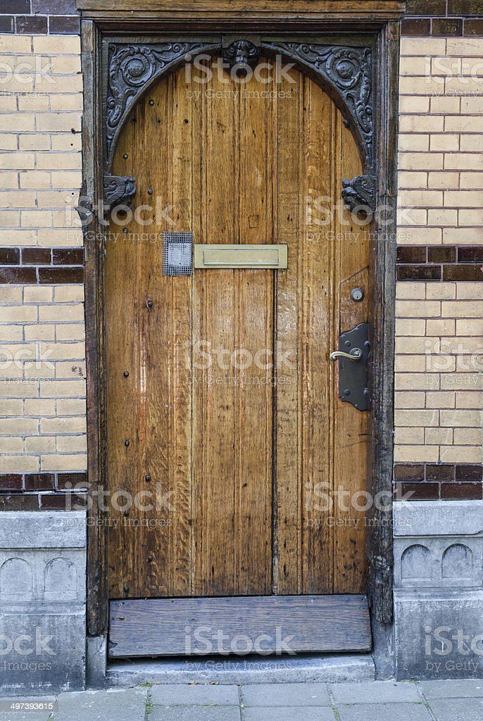 An old brick wall with light brown wooden door stock photo