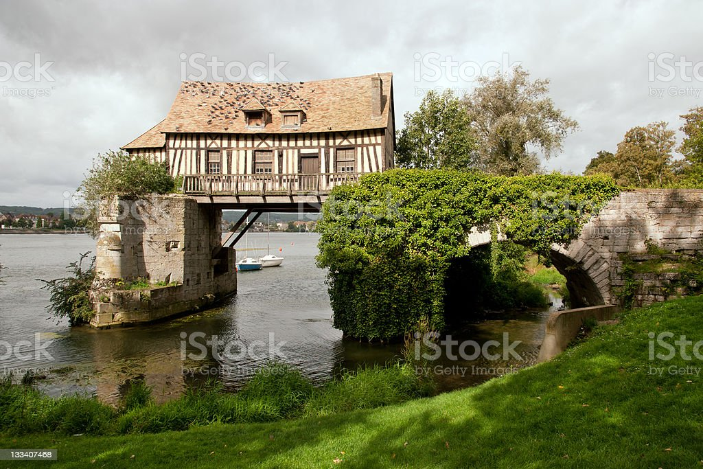 An old cottage hovering over a lake in a green landscape stock photo
