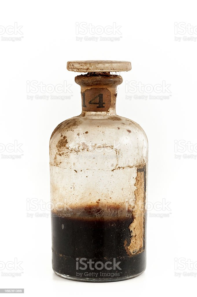 An old glass bottle half filled with brown poison stock photo