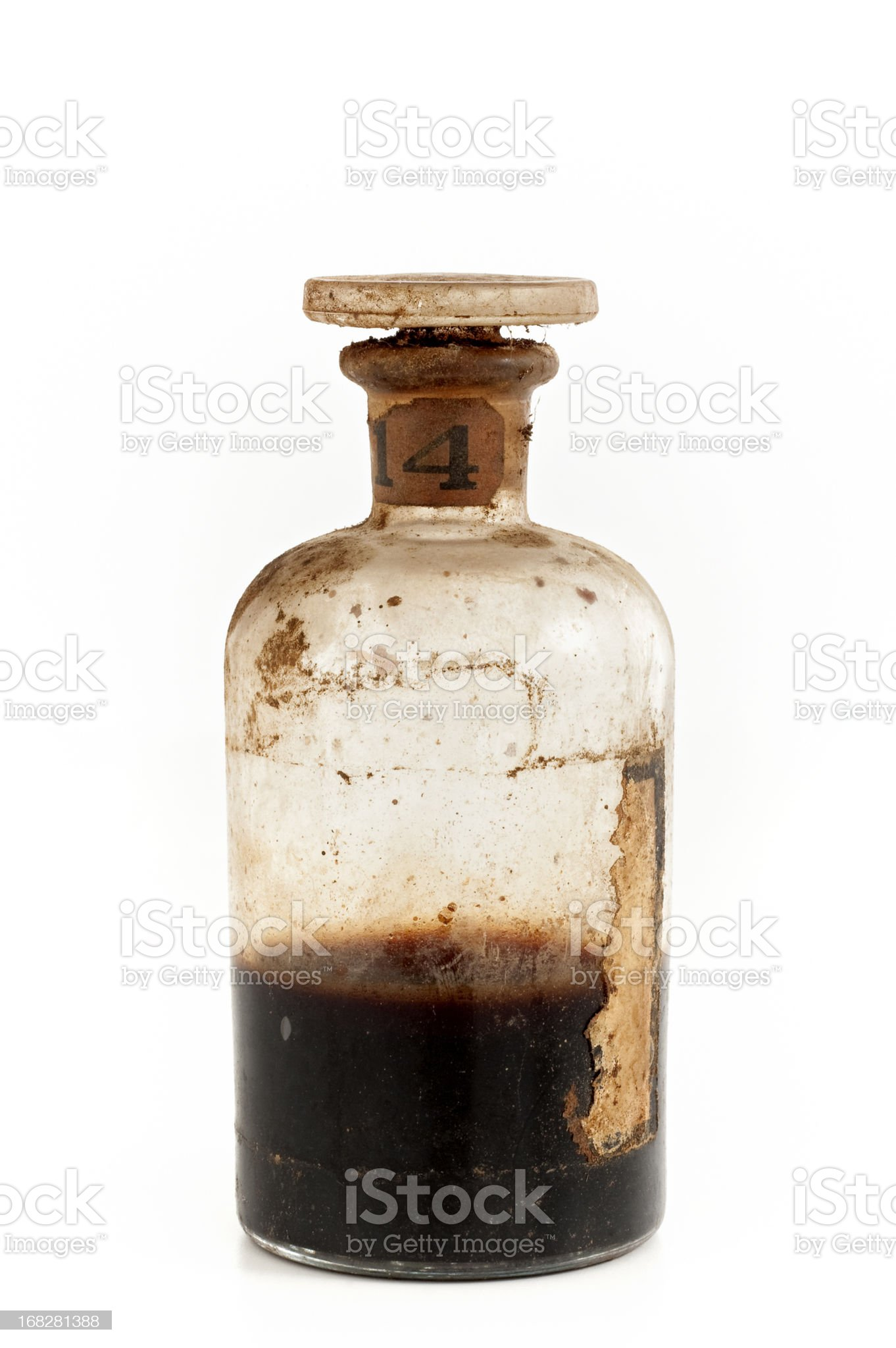 An old glass bottle half filled with brown poison royalty-free stock photo