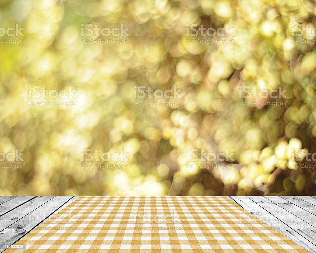 An old grey picnic table with a yellow tablecloth  royalty-free stock photo