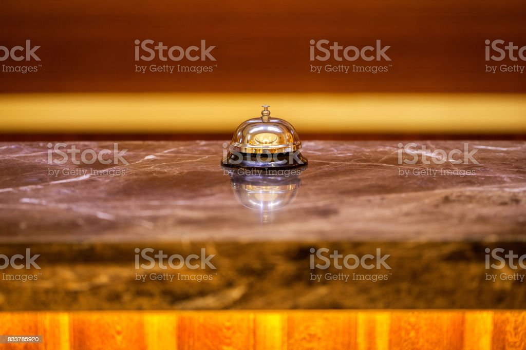 an old hotel bell on a marble stand stock photo