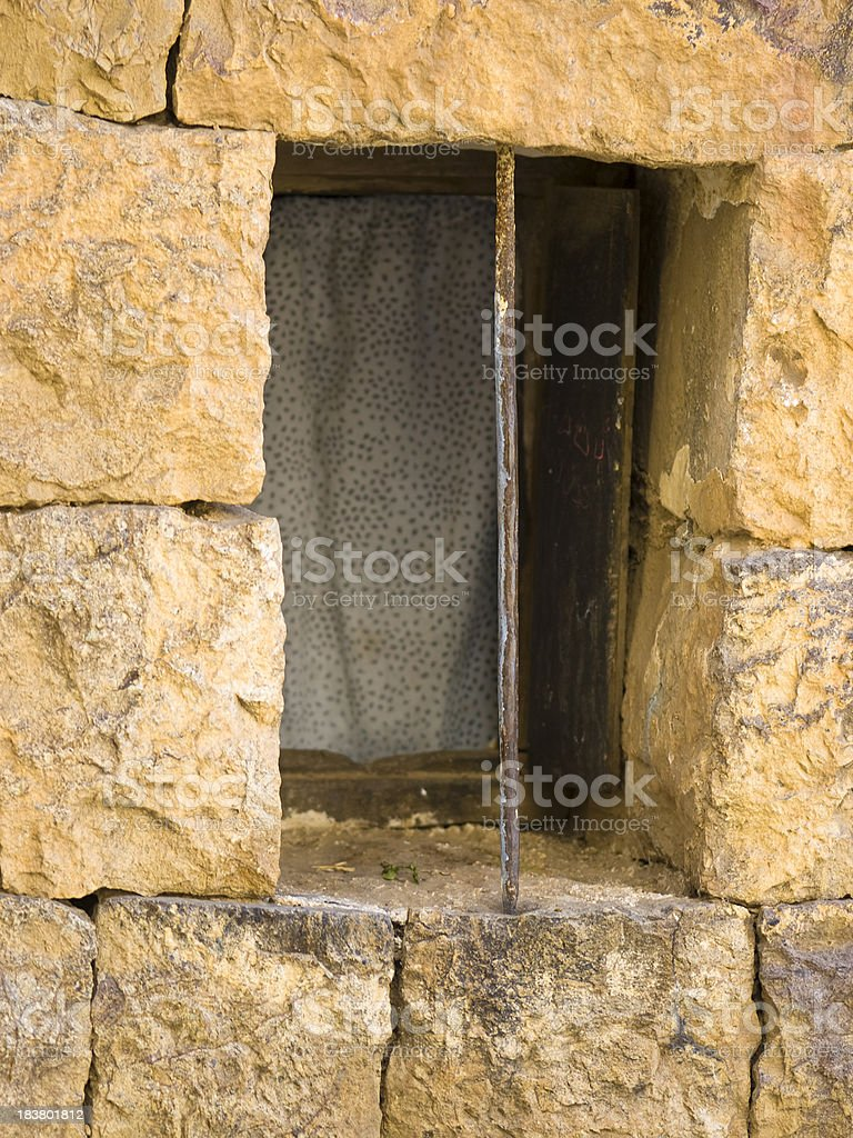 An old house window snug in a rock wall. royalty-free stock photo