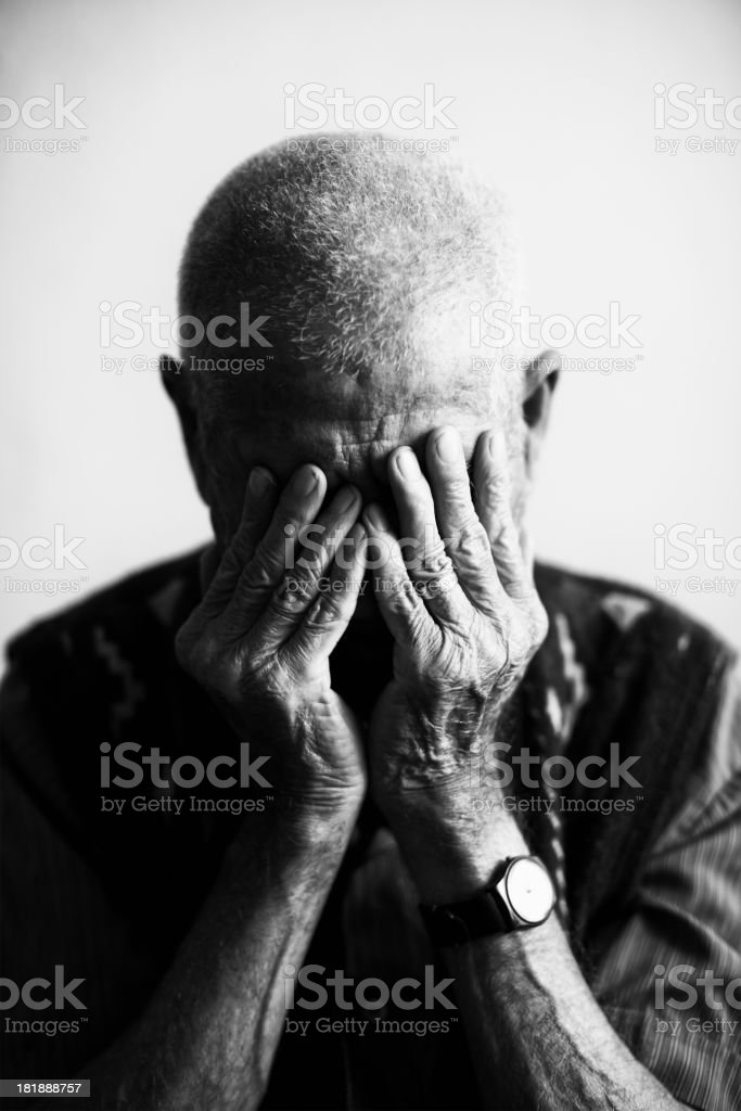 An old man covering his face with his hands in grief  stock photo