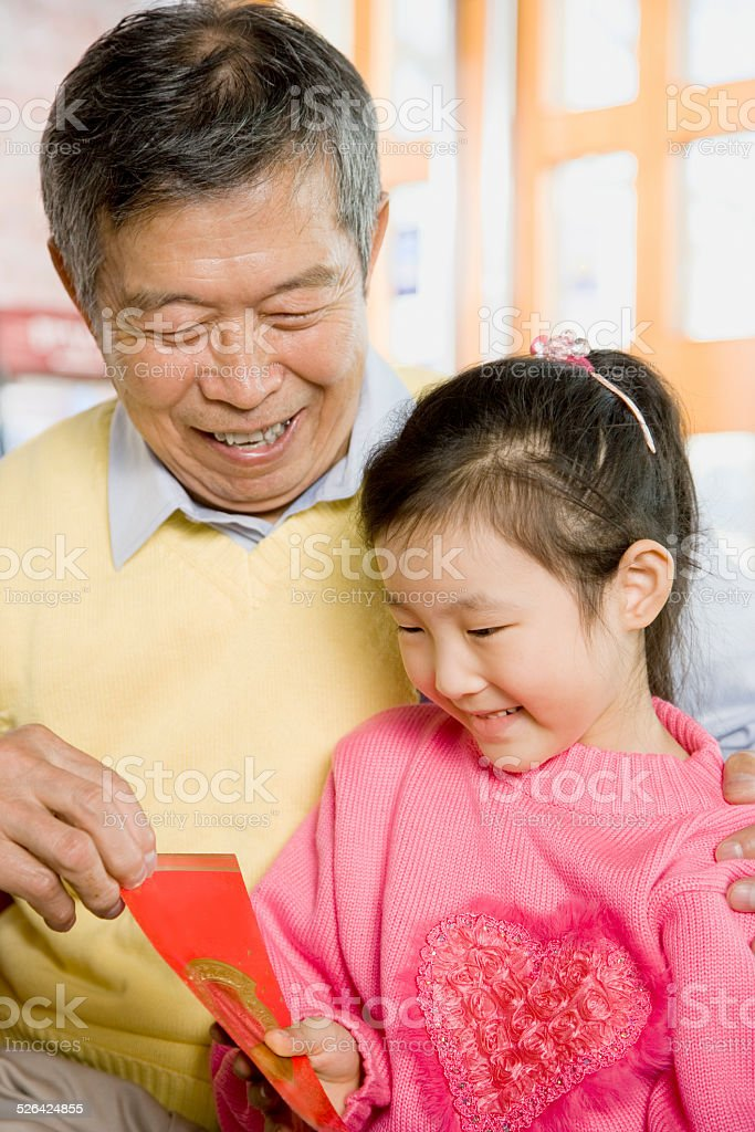 An Old Man Giving Red Packet to Little Girl stock photo