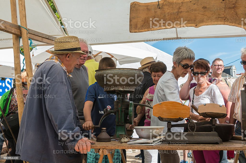 an old man operates an ancient machine to grind grain stock photo
