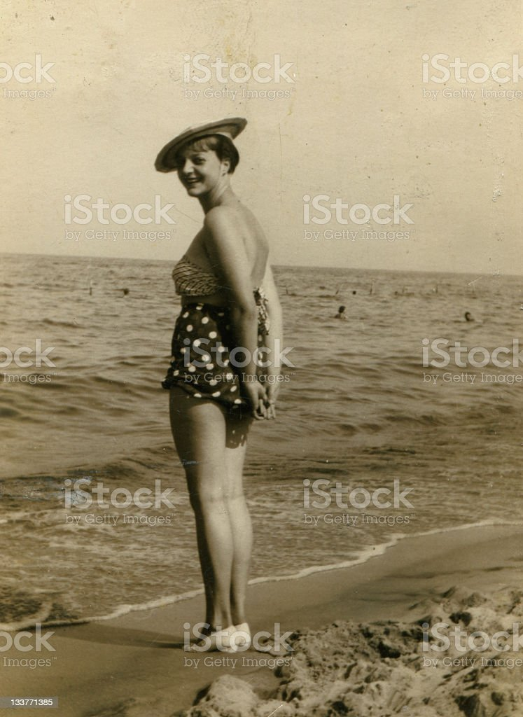 An old photograph of a woman in a bathing suit on the beach stock photo