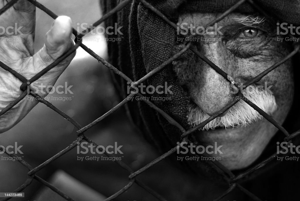 An old prisoner looking through a fence stock photo