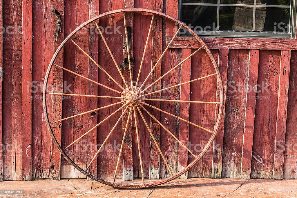 An old red barn and wagon wheel stock photo