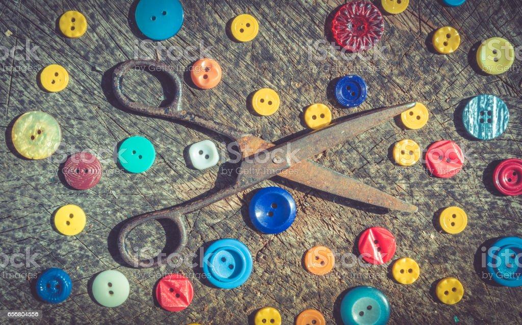 Старинный набор для рукоделия. Старые ржавые ножницы и разноцветные пуговицы. Набор портного в стиле ретро stock photo