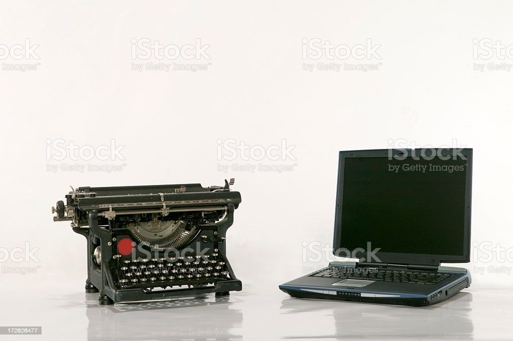 An old typewriter next to a new laptop on a white background stock photo