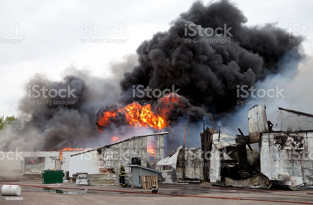 An old warehouse on fire with black smoke  stock photo