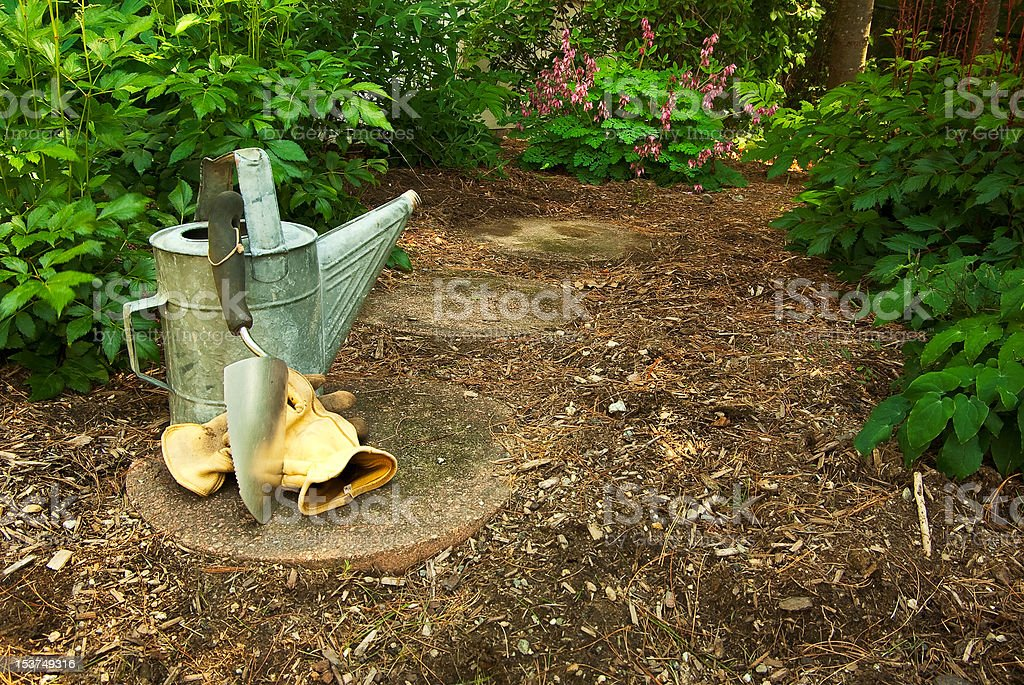 An Old Watering Can with Trowl and Work Gloves stock photo