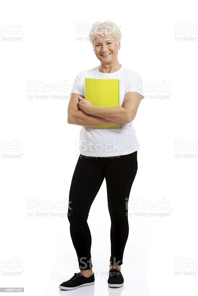 An old woman holding workbook and showing OK. stock photo