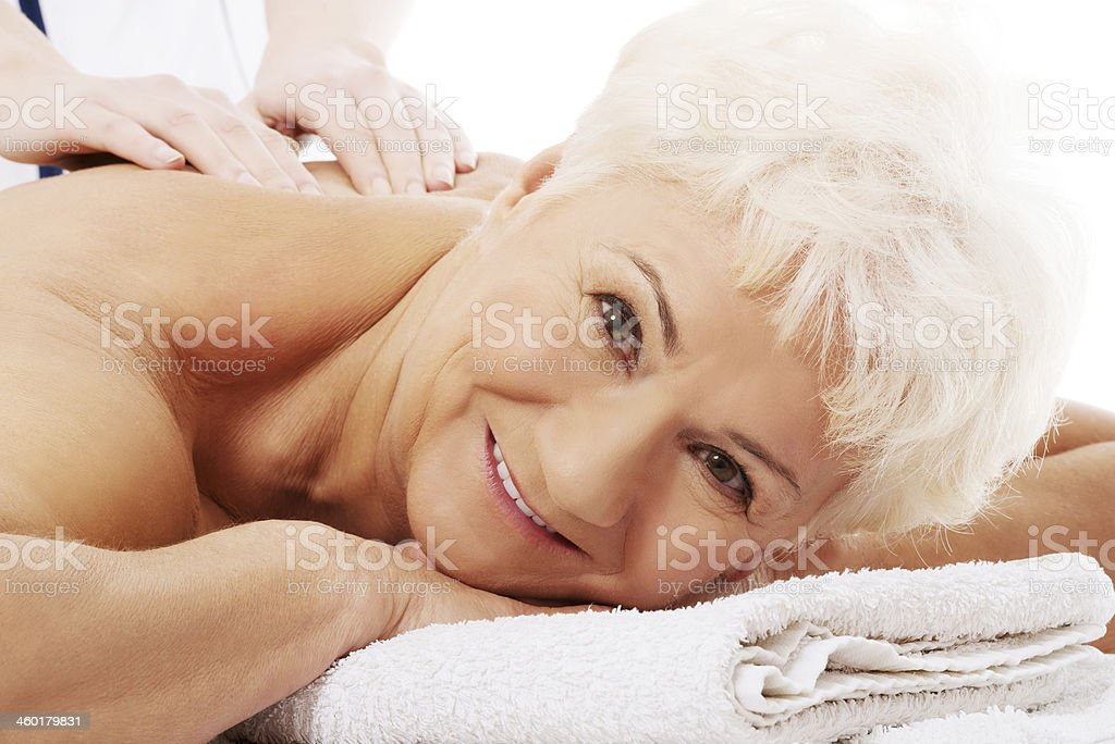 An old woman is having a massage. Spa concept. stock photo