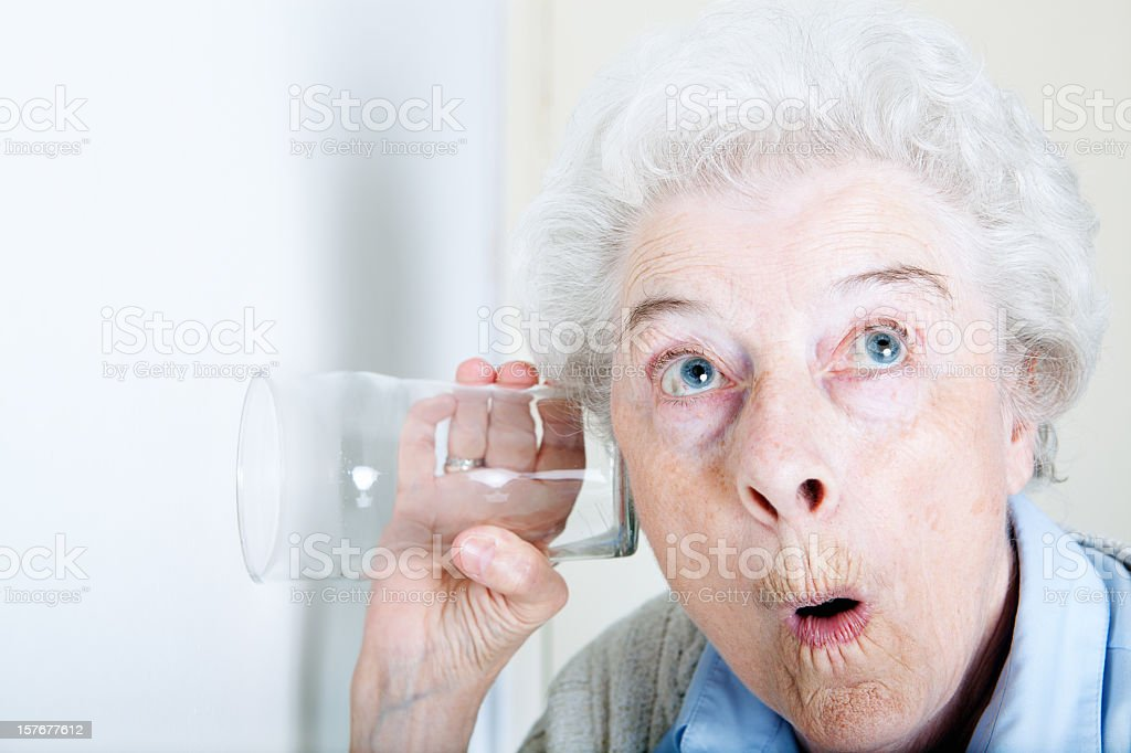 An old woman looking shocked with a glass on her ear stock photo