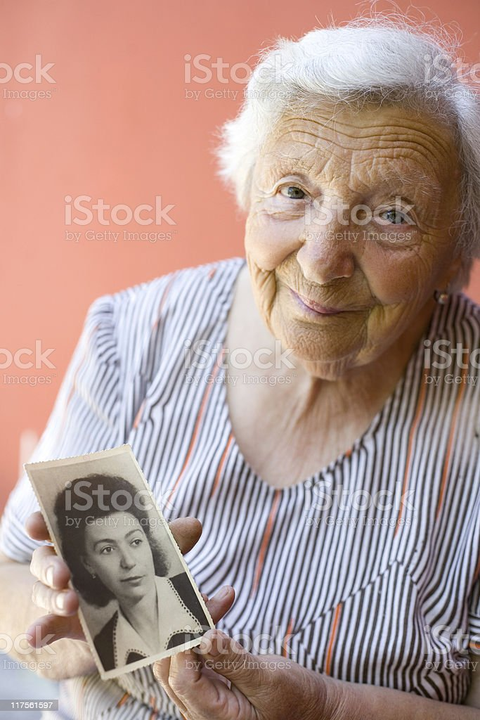 An old woman smiling with holding a portrait from her youth royalty-free stock photo