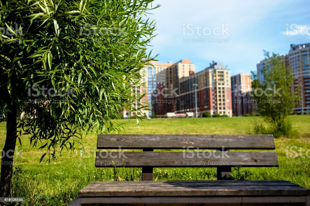 An old wooden bench in the park against a background of blurry trees and buildings. stock photo