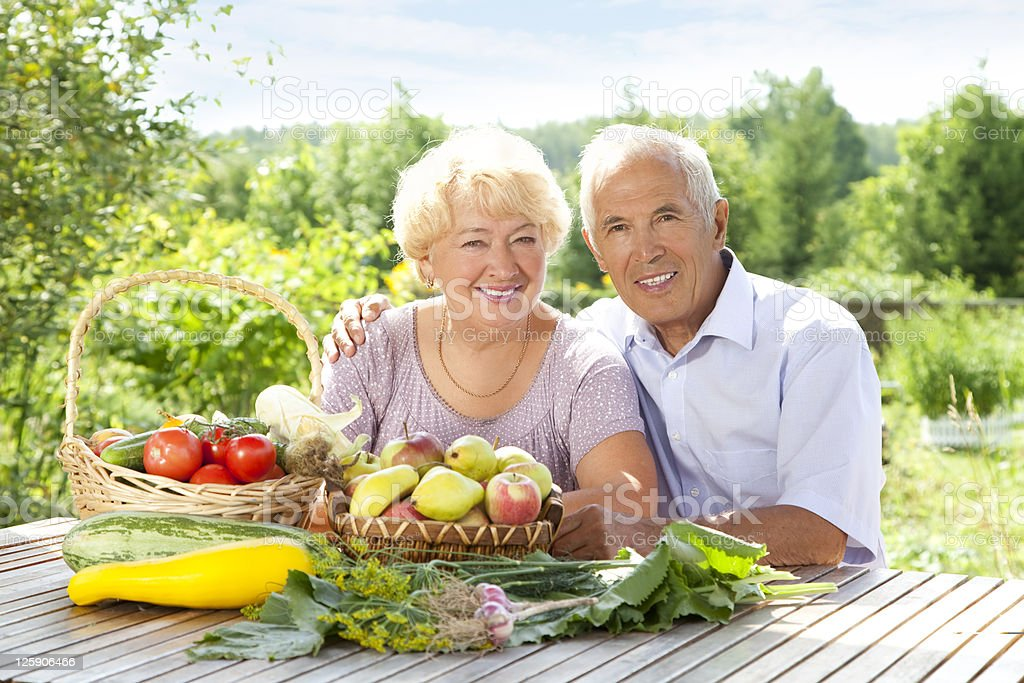 An older couple with baskets of fruit and vegetables royalty-free stock photo