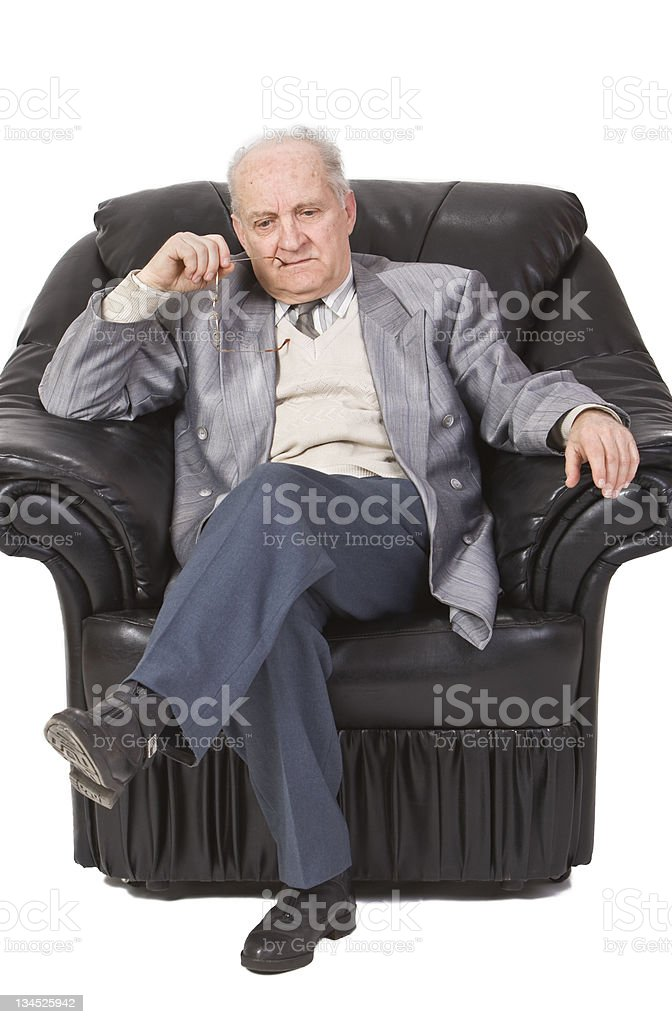 An older man in leather arm chair glasses in hand and mouth. royalty-free stock photo