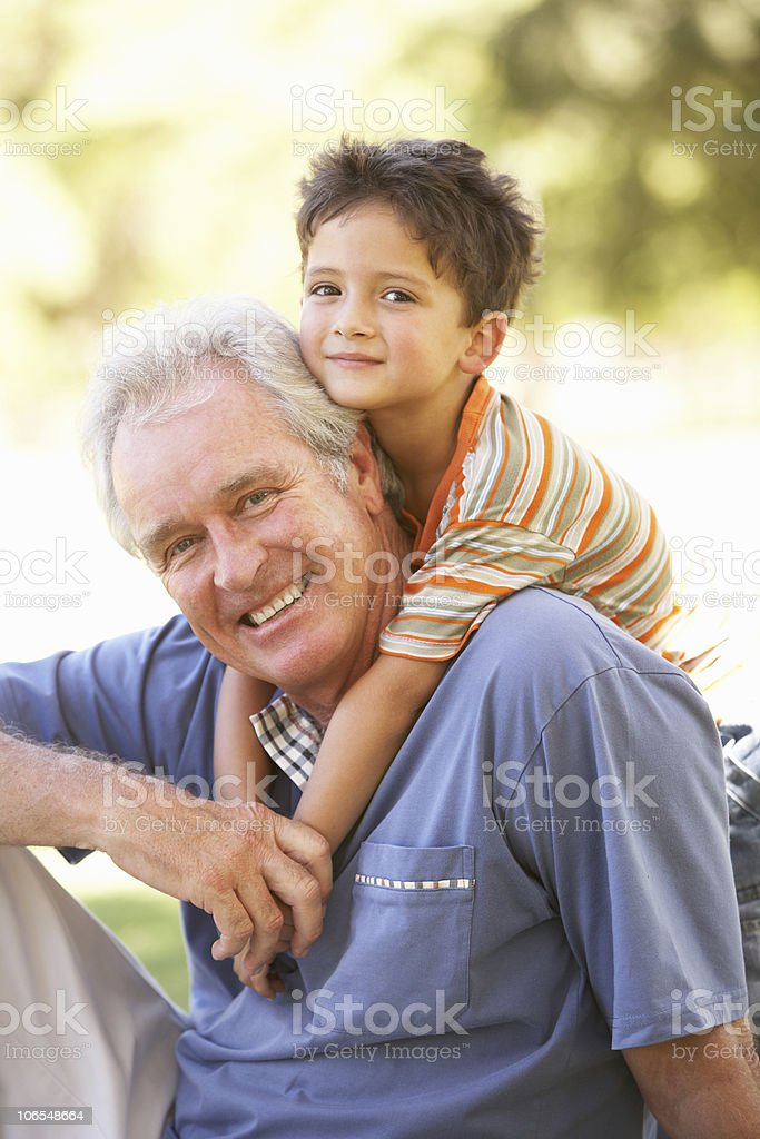 An older man with a small child on his back stock photo