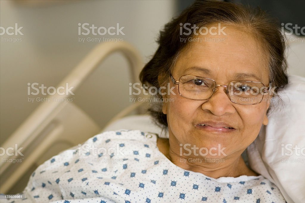 An older woman in a hospital gown laying on a bed  stock photo