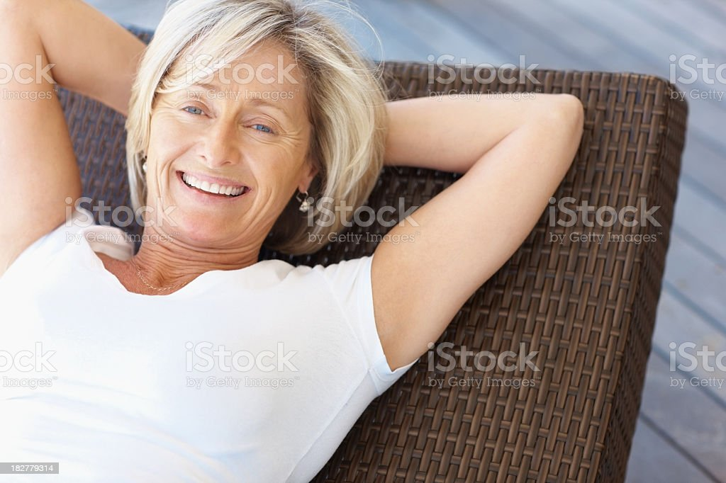 An older woman smiles and lies on a lawn chair royalty-free stock photo