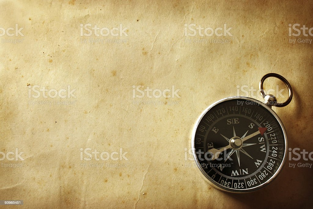 An old-fashioned compass on a wooden table not being used stock photo