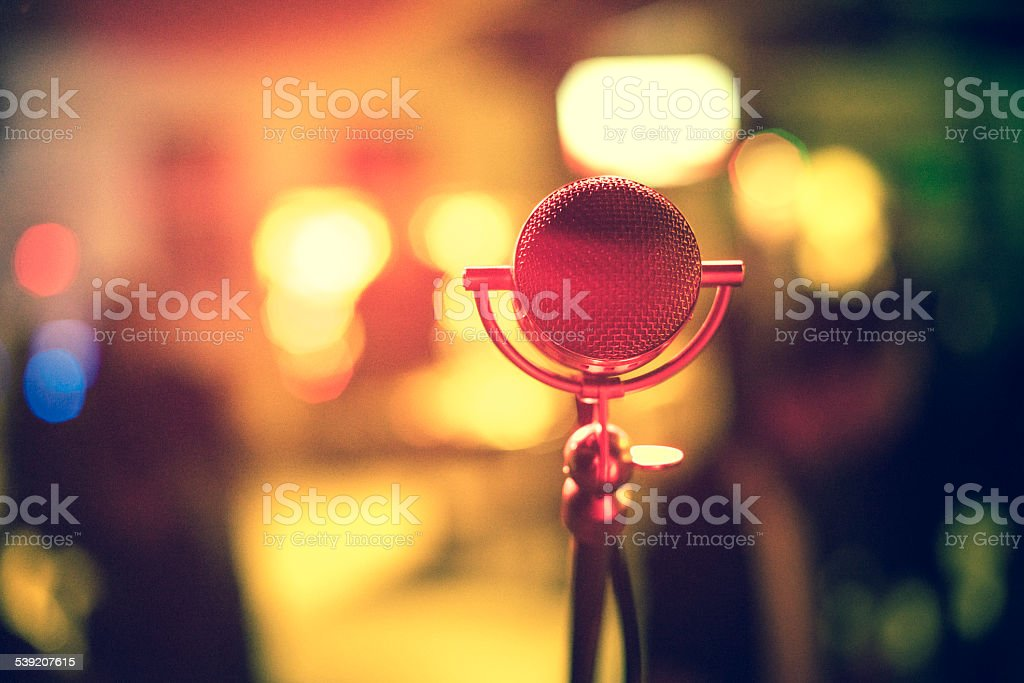 An old-fashioned metal microphone with blurred lights. stock photo