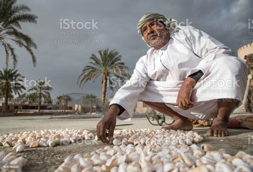 An Omani man laying out sea shells. stock photo