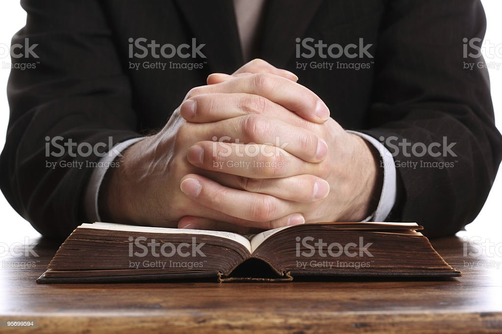 An open bible with a praying hands stock photo