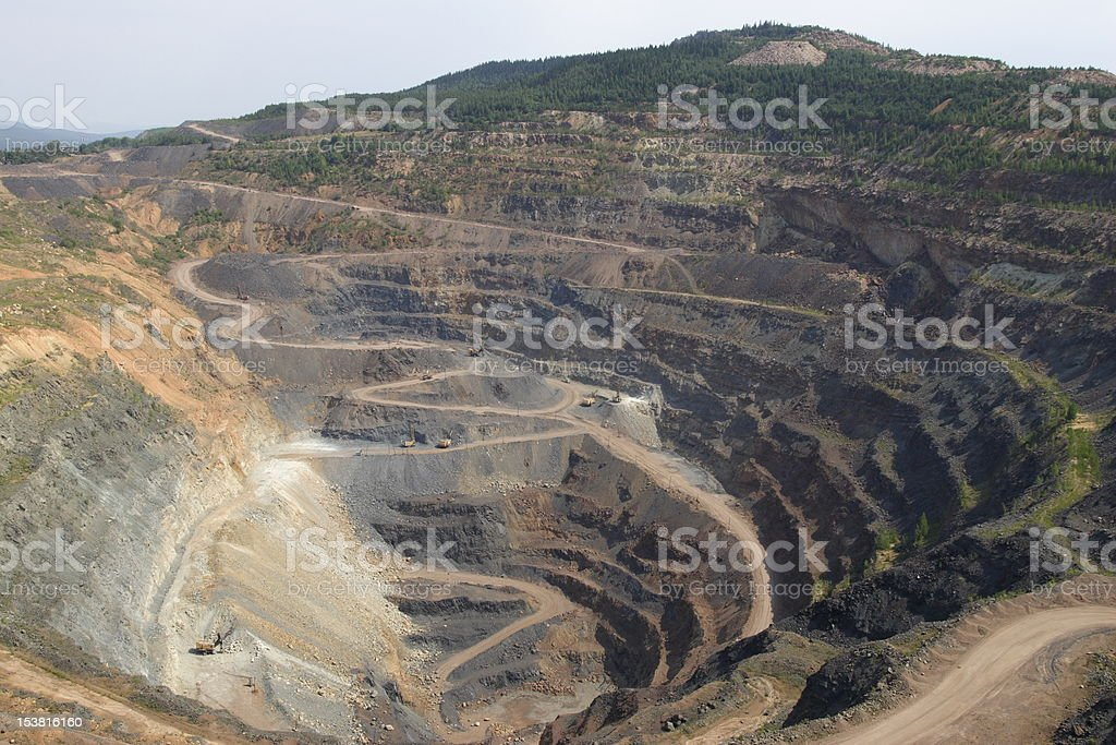 An open ore mine pit with dirt pathways traveling through it stock photo