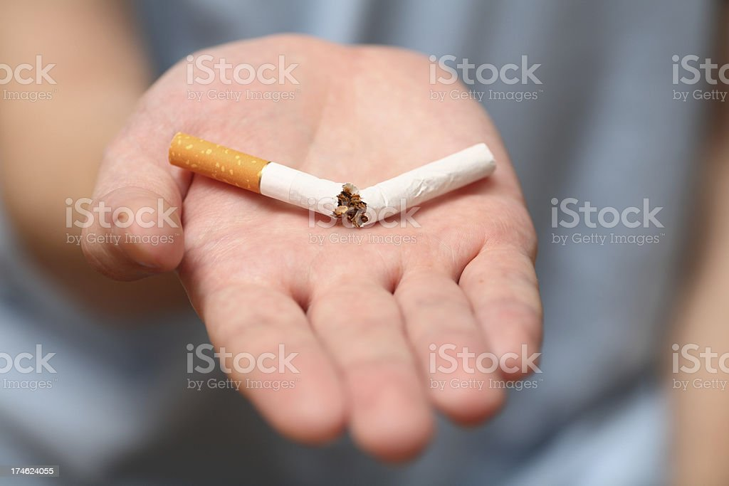 An open palm with a broken cigarette royalty-free stock photo