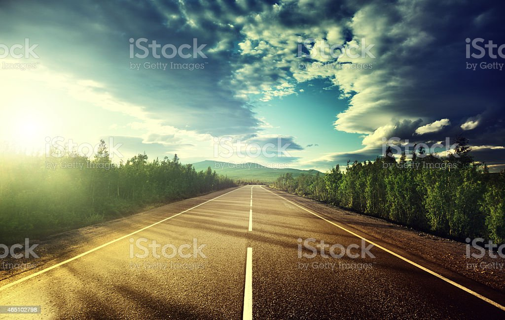 An open road lined with trees in the mountains stock photo