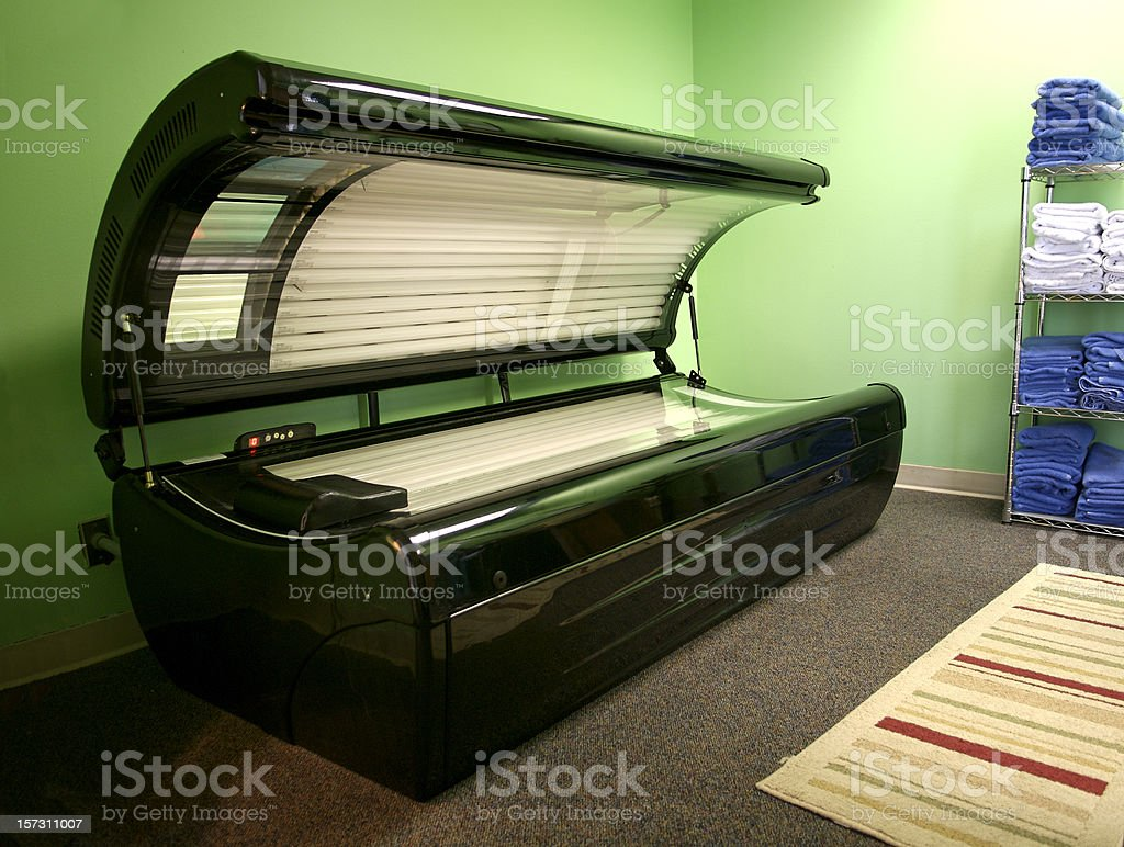 An open tanning bed in a green room stock photo