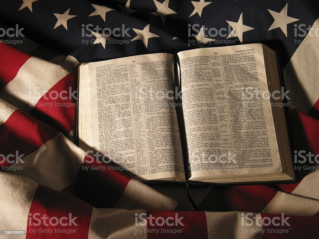 An opened Bible on top of the American flag stock photo