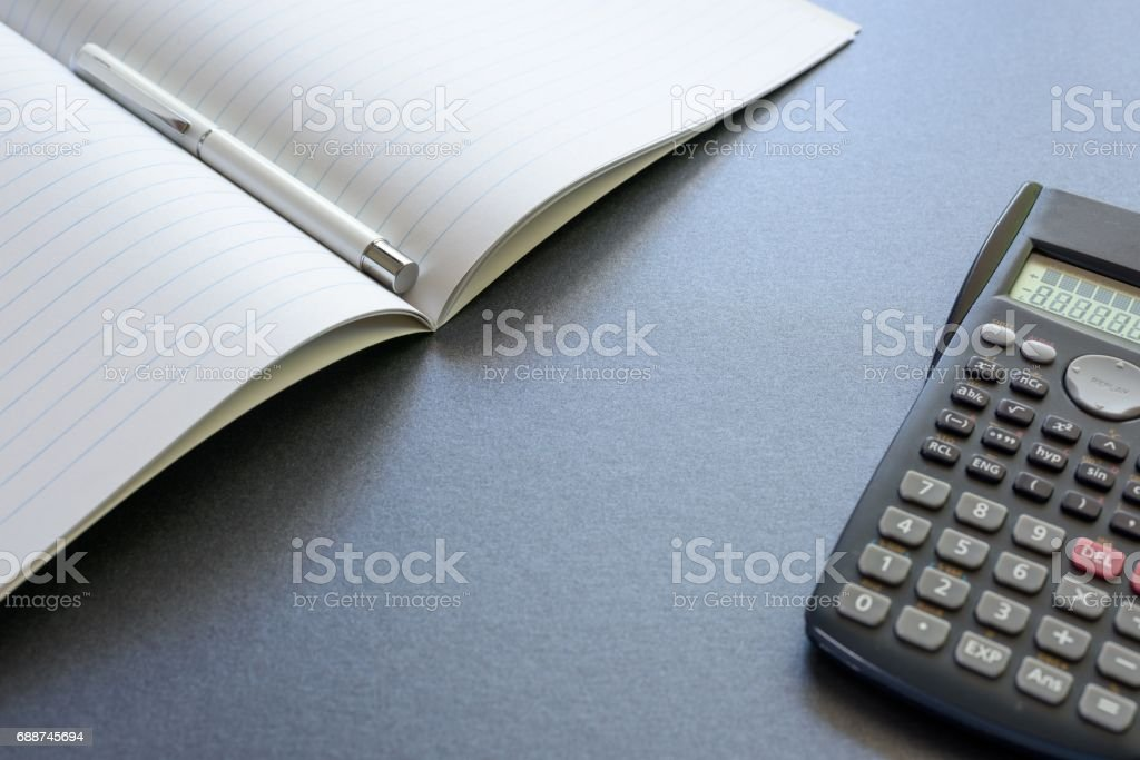 An opened notebook with a pen and a calculator, on dark grey background, scene school or office. stock photo