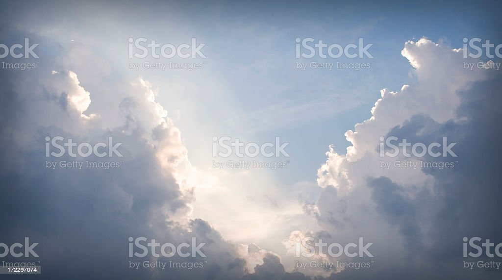 An opening in grey clouds revealing sunlight showing the way stock photo