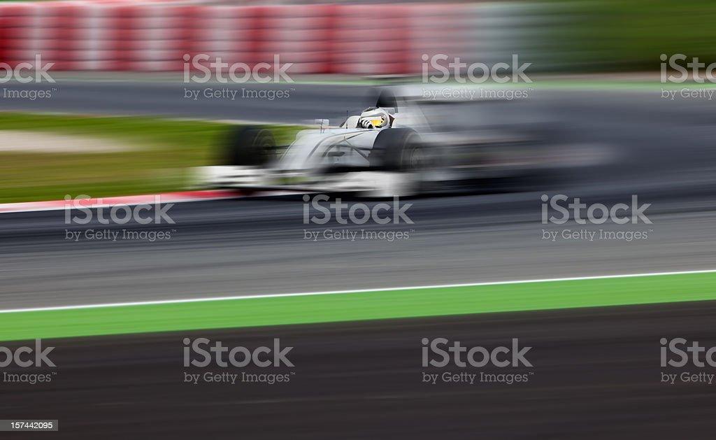 An open-wheel race car in motion stock photo