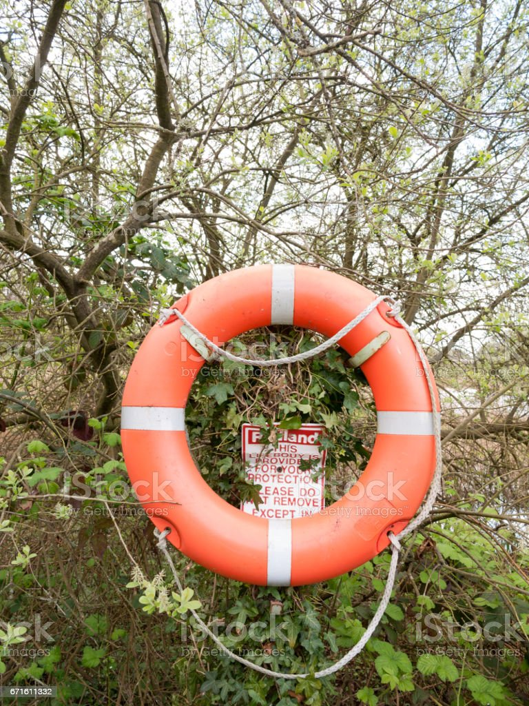 an orange and silber life buoy with rope with a safety sign behind it in the forest next to a lake stock photo